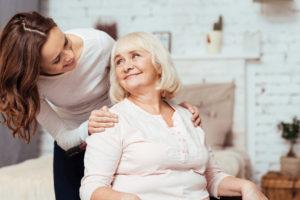 Pflegerin steht pflegebedürftigen Person bei