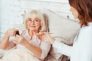 Pflegekraft klärt Patientin über Medikamente auf